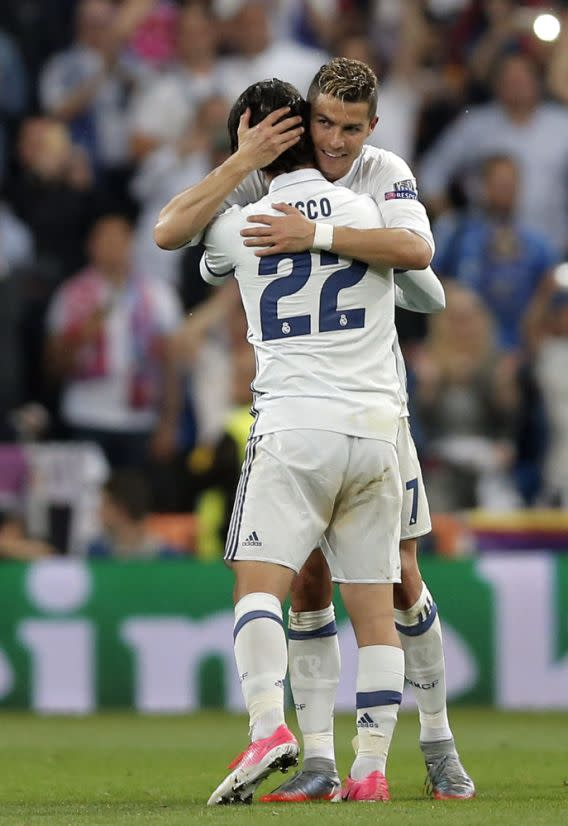 Real Madrid's Cristiano Ronaldo, right, celebrates with teammate Isco at the end of the Champions League semifinals first leg soccer match between Real Madrid and Atletico Madrid at Santiago Bernabeu stadium in Madrid, Spain, Tuesday May 2, 2017. Ronaldo scored all three goals in Real Madrid's 3-0 win. (AP Photo/Daniel Ochoa de Olza)