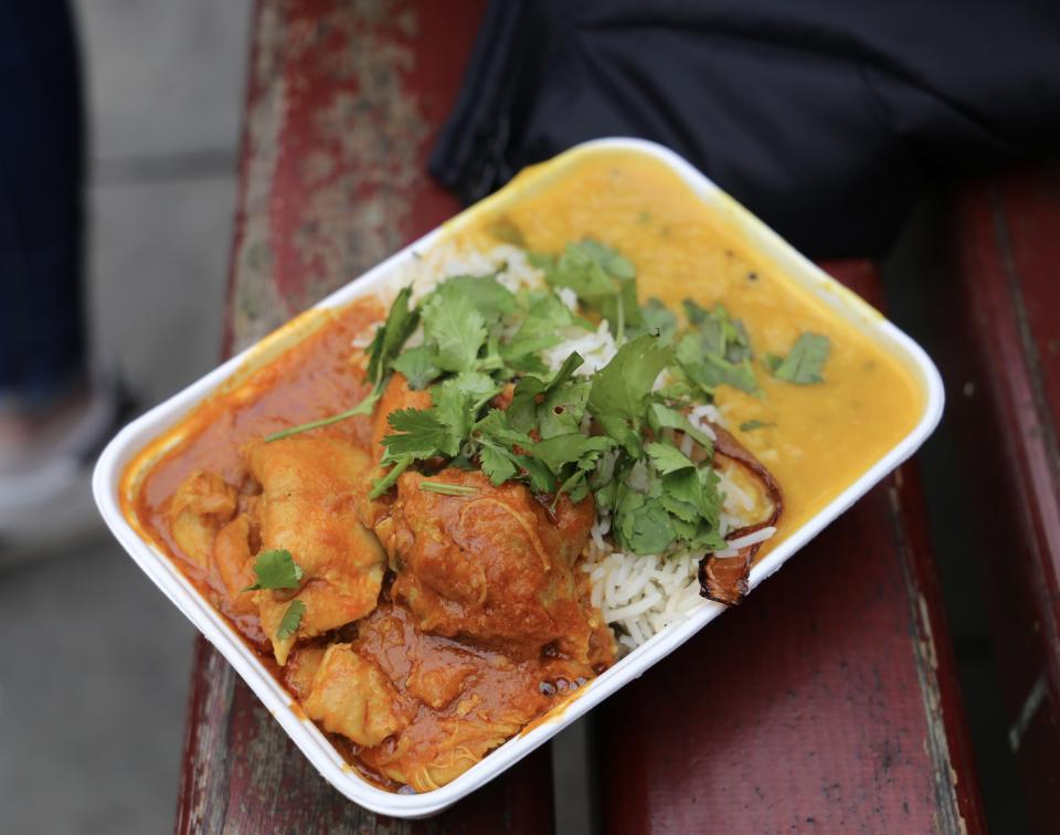 Freshly made curry and rice in a cardboard takeaway container sold at Manchester Christmas markets.