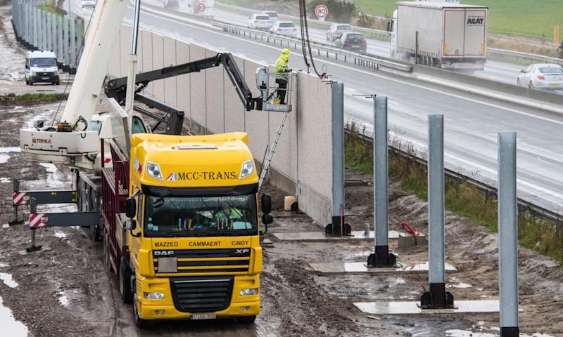 Workers build the 1km 'Great Wall of Calais' aimed at preventing refugees from trying to reach Britain.