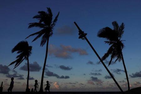 People are seen in silhouette walking on a beach affected by Hurricane Maria in San Juan, Puerto Rico, October 13, 2017. REUTERS/Shannon Stapleton/Files
