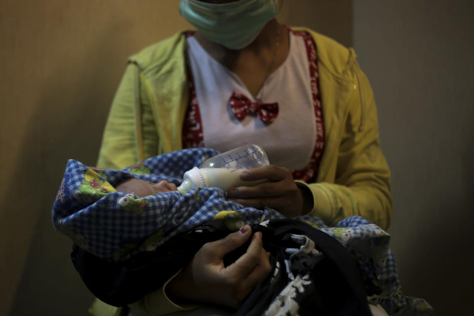 "A 17-year-old mother gives a bottle to her 2-week-old baby, whom she says was born as a result of a rape in Sumatra, Indonesia, Sunday, Sept. 9, 2018. She started working on a plantation as a young child to help her family survive, never going to school or learning how to read or write. One day she said her boss took her alone to a quiet part of the estate. After the attack, while still half-naked, she said the man held a blade to her throat. ""He threatened to kill me with an ax. ... He threatened to kill my whole family."" Then, she said, he stood up, spit on her and walked away. (AP Photo)"