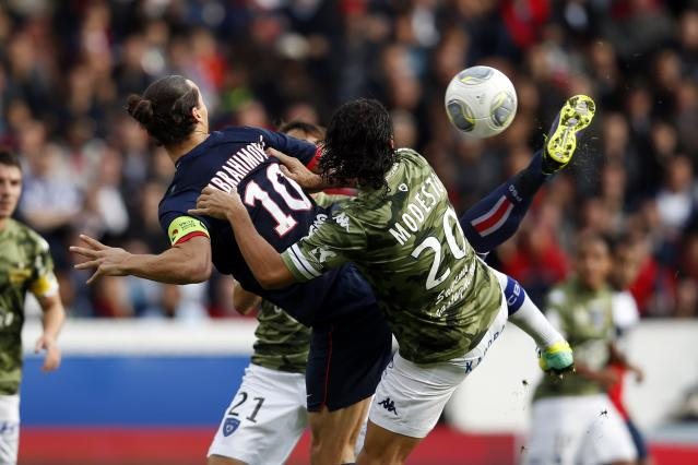 Paris St Germain's Zlatan Ibrahimovic challenges Bastia's Francois-Joseph Modesto (R) and scores his first goal during their French Ligue 1 soccer match at the Parc des Princes Stadium in Paris October 19, 2013. REUTERS/Benoit Tessier (FRANCE - Tags: SPORT SOCCER)
