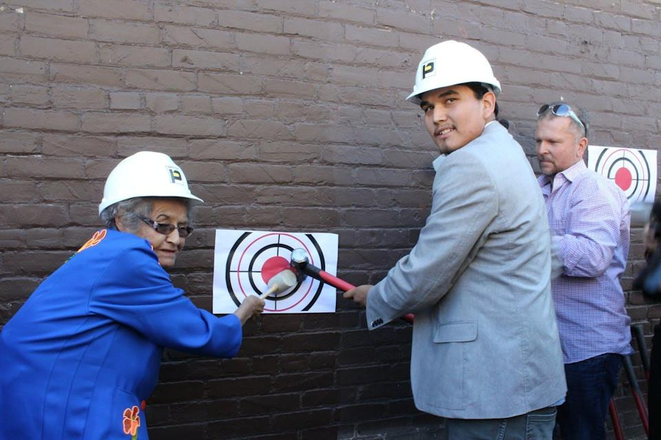 An elder and a young man are seen wearing hard hats smiling and swinging a hammer against a brick wall.
