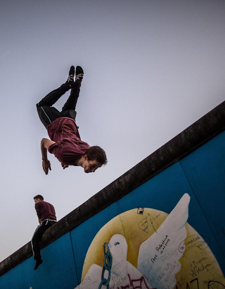 """A man rehearses as part of """"Circus transcends borders"""" at the East Side Gallery on November 8, 2014 in Berlin, on the eve of the 25th anniversary of the fall of the Berlin Wall."""