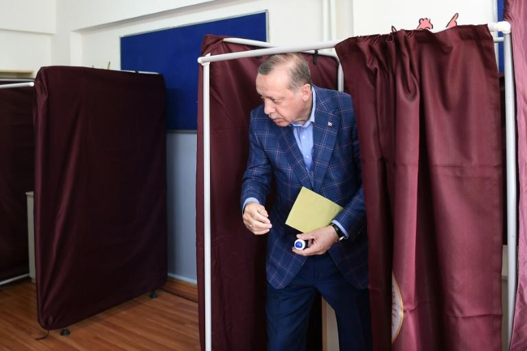 Turkish President Recep Tayyip Erdogan holds his ballot as he leaves a booth to cast his vote in the referendum on expanding the powers of the president at a polling station in the Uskudar district of Istanbul, on April 16, 2017