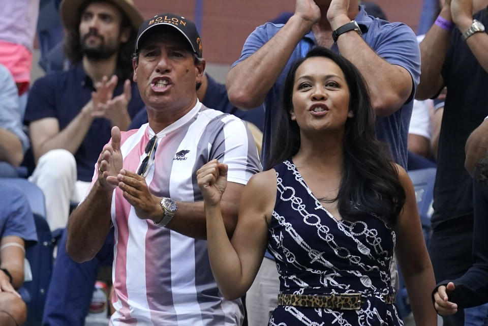 Duglas Cordero, left, fitness coach for Leylah Fernandez, of Canada, and Irene Exevea, Fernandez's mother, cheer her on during the women's singles final of the US Open tennis championships against Emma Raducanu, of Britain, Saturday, Sept. 11, 2021, in New York. (AP Photo/Seth Wenig)