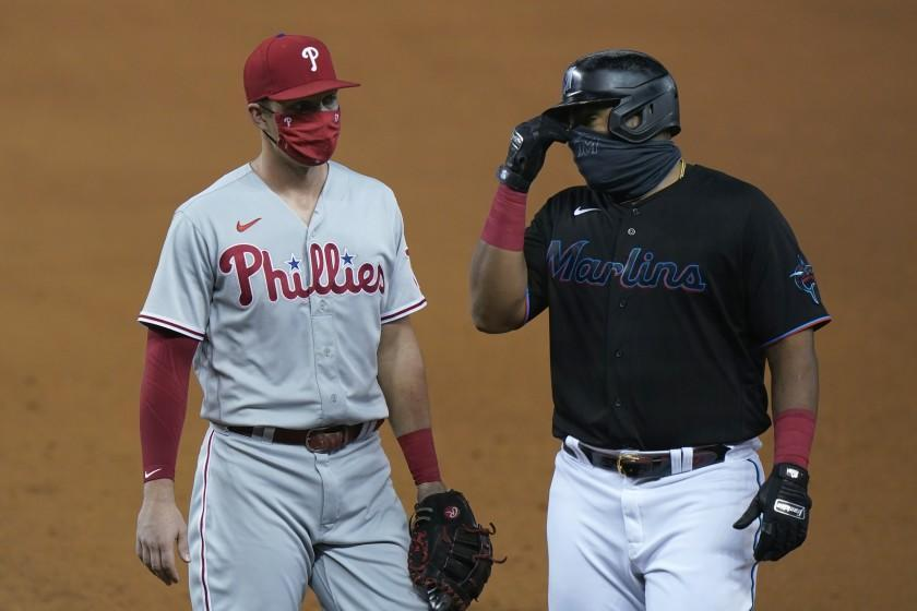 Wearing masks to help prevent the spread of the new coronavirus, Philadelphia Phillies first baseman Rhys Hoskins, left, talks with Miami Marlins' Jesus Aguilar during the fourth inning of a baseball game, Saturday, Sept. 12, 2020, in Miami. (AP Photo/Wilfredo Lee)