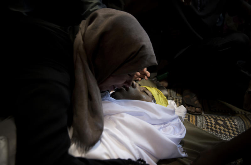 A relative of Palestinian, Mohammed Abbas, 21, who was killed by Israeli troops during Friday's protest at the Gaza Strip's border with Israel, mourns over his body at the family home during his funeral in Gaza City, Saturday, Oct. 13, 2018. (AP Photo/Khalil Hamra)