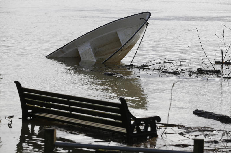 A boat and a bench are submerged in water, in Shepperton, England, Tuesday, Feb. 11, 2014. The River Thames has burst its banks after reaching its highest level in years, flooding riverside towns upstream of London. Residents and British troops piled up sandbags to protect properties from the latest bout of flooding, but the river overwhelmed their defenses in several places Monday, leaving areas underwater. (AP Photo/Sang Tan)
