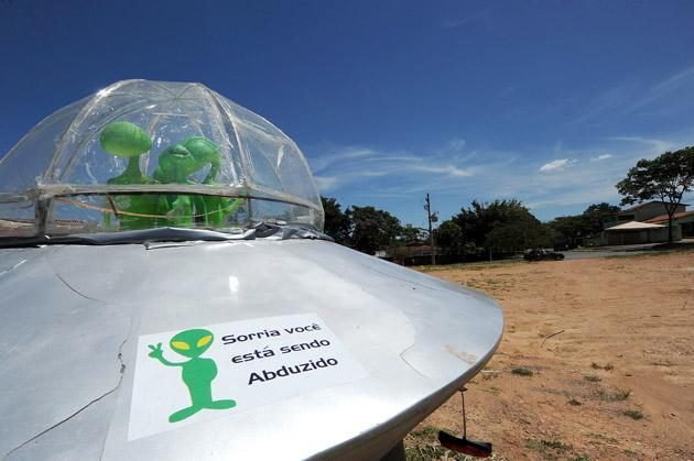 "A mock UFO with alien dolls and reading ""Smile, you are being abducted"" is seen in Alto Paraiso town, Goias State, 230 kms north of Brasilia, on December 20, 2012. Situated over a huge quartz crystal plate, Alto Paraiso attracted many Brazilians and foreigners seeking refuge from the events expected by the Mayan prophecy that predicts the end of the world or the beginning of a new era. AFP PHOTO / Evaristo SA"