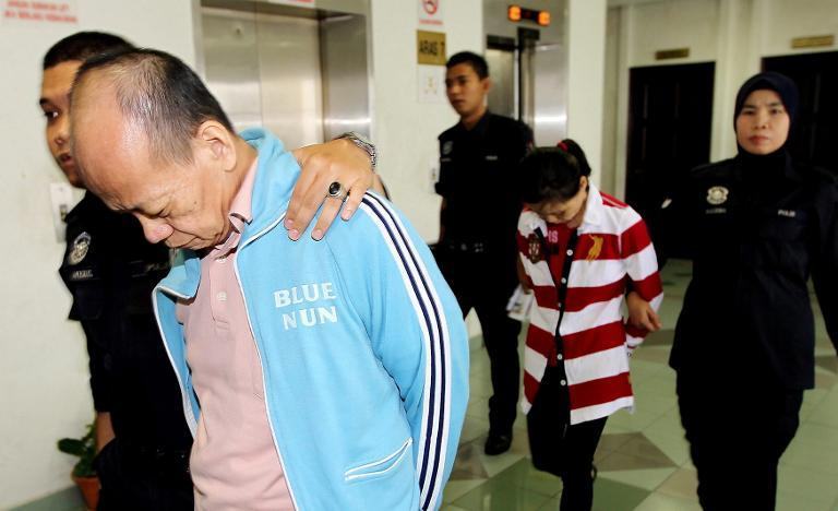 Police escort Fong Kong Meng, 58, (front R) and his wife Teoh Ching Yen, 56, (back C) at the Malaysian high court in Shah Alam, outside Kuala Lumpur after they were sentenced to death for killing their Indonesian maid