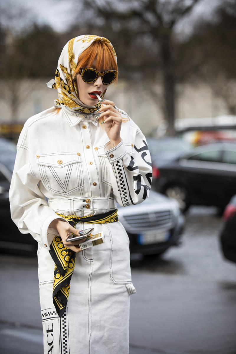 PARIS, FRANCE - MARCH 02: A guest, wearing a white denim Versace jacket with matching Versace skirt, beige boots and printed hair scarf, is seen outside Haider Ackermann on Day 6 Paris Fashion Week Autumn/Winter 2019/20 on March 2, 2019 in Paris, France. (Photo by Claudio Lavenia/Getty Images)