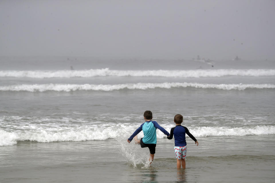 """FILE - In this April 26, 2020, file photo, two young visitors wade in the surf in Huntington Beach, Calif. As some governors across the United States begin to ease restrictions imposed to stop the spread of the coronavirus, hopes are soaring that life as we knew it might be returning. But the plans emerging in many states indicate that """"normal"""" is still a long way off. (AP Photo/Marcio Jose Sanchez, File)"""