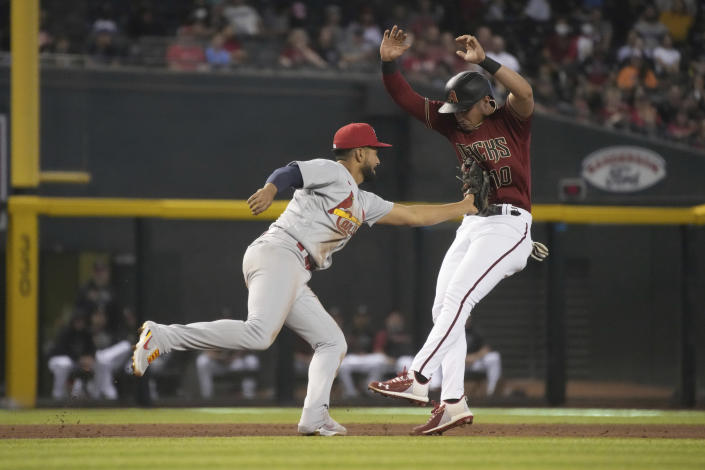 Arizona Diamondbacks' Josh Rojas, right, gets tagged out by St. Louis Cardinals third baseman Jose Rondon, left, on a ball hit by Carson Kelly in the fourth inning during a baseball game, Sunday, May 30, 2021, in Phoenix. (AP Photo/Rick Scuteri)