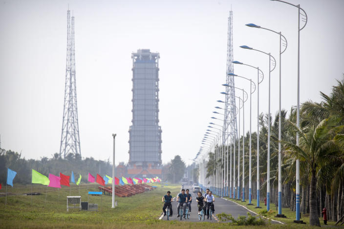 People ride bicycles along a road near a launch pad at the Wenchang Space Launch Site in Wenchang in southern China's Hainan province, Monday, Nov. 23, 2020. Chinese technicians were making final preparations Monday for a mission to bring back material from the moon's surface for the first time in nearly half a century — an undertaking that could boost human understanding of the moon and of the solar system more generally. (AP Photo/Mark Schiefelbein)
