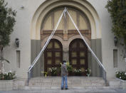 FILE - In this Sunday, April 12, 2020, file photo, a parishioner prays outside the closed doors decorated with Easter lily flowers at the Christ the King Church Roman Catholic Church in Los Angeles. A federal appeals court has denied a Southern California church's request to overturn the state's coronavirus restrictions barring worship services indoors during the coronavirus pandemic. The Sacramento Bee says Friday, Jan. 22, 2021, ruling by the 9th U.S. Circuit Court of Appeals leaves the door open for addressing Gov. Gavin Newsom administration's limits on church attendance if a California county is in a less-restrictive COVID-19 tier. (AP Photo/Damian Dovarganes, File)