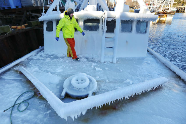 <p>With temperatures in the single digits, Ray Levesque, mate of the crab/lobster boat Bradbill, makes his way across the deck covered in ice to tie off, after arriving in New Bedford, Mass., harbor on Thursday, Dec. 28, 2017, from a one day fishing voyage. (Peter Pereira/Standard Times via AP) </p>