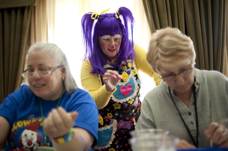 """In a July 31, 2012 photo, Deanna Hartmier, aka """"Dee Dee"""" the clown, center, offers tips to Patricia Jannell, aka """"PJ"""" the clown, and Carol Feldhelm, aka """"Dizzy Daizy"""" the clown, during a face painting class at the third annual Clown Campin' in Ontario, Calif. The week long event is held for clowns across the United States and Canada to learn, get inspired, and network. (AP Photo/Grant Hindsley)"""