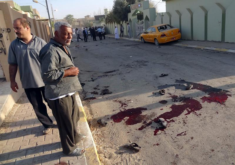 Worshipers look at blood stains at the site of a bomb attack near a Sunni mosque in Kirkuk, 290 kilometers (180 miles) north of Baghdad, Iraq, Tuesday, Oct. 15, 2013. A bomb ripped through a crowd of Sunni worshippers coming out of a mosque in northern Iraq after prayers at the start of a major Muslim holiday on Tuesday, killing and wounding dozens of people, Iraqi officials said. (AP Photo/Emad Matti)