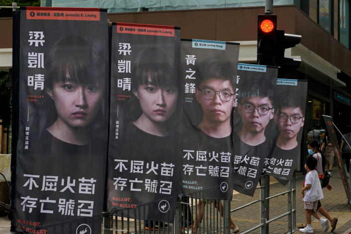 FILE - In this July 11, 2020, file photo, banners of a pro-democracy candidate Joshua Wong, wearing glasses, are displayed outside a subway station in Hong Kong, in an unofficial primary for pro-democracy candidates ahead of legislative elections. About 50 Hong Kong pro-democracy figures were arrested by police on Wednesday, Jan. 6, 2021 under a national security law, following their involvement in an unofficial primary election last year held to increase their chances of controlling the legislature, according to local media reports. (AP Photo/Vincent Yu,File)