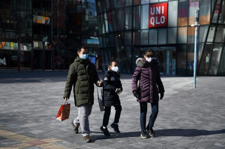 A family wears protective face masks outside an almost-empty Beijing shopping mall (AFP Photo/GREG BAKER)
