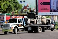 Tow truck transports the burnt wreckage of a police patrol truck a day after cartel gunmen clashed with federal forces in Culiacan