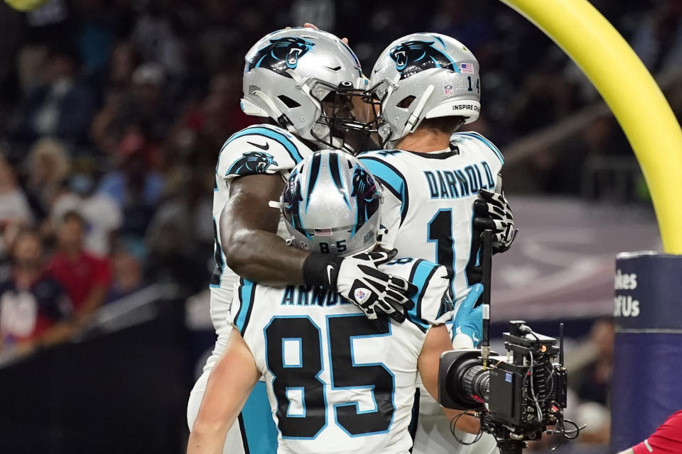 Carolina Panthers quarterback Sam Darnold (14) celebrates his touchdown run with Dan Arnold (85) and Cameron Erving (75) during the first half of an NFL football game Thursday, Sept. 23, 2021, in Houston. (AP Photo/Eric Christian Smith)