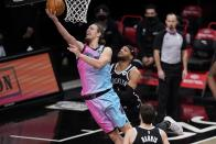Miami Heat's Kelly Olynyk, left, drives past Brooklyn Nets' Bruce Brown, center, and Joe Harris during the second half of an NBA basketball game Saturday, Jan. 23, 2021, in New York. (AP Photo/Frank Franklin II)