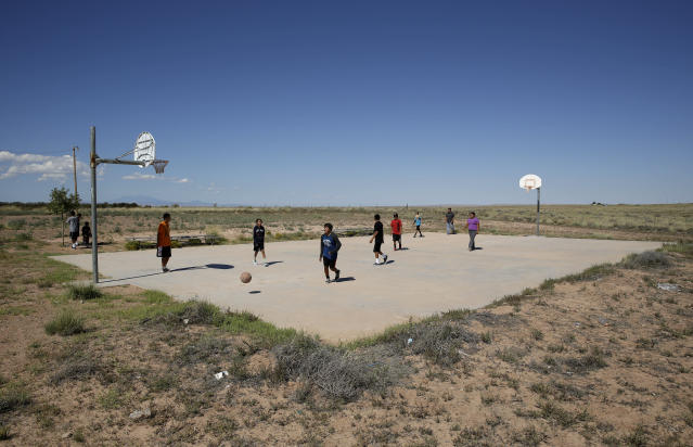 FILE - In this Sept. 25, 2014, file photo, students play basketball at Little Singer Community School in Birdsprings, Ariz., on the Navajo Nation. Basketball is woven in the fabric of Native American life. Now, during a global pandemic, the balls have all but stopped bouncing. Already hit hard by the coronavirus outbreak, Native Americans are faced with life without basketball or any other sport - for the forseeable future. (AP Photo/John Locher, File)