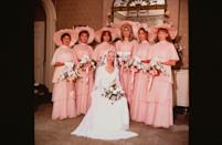 <p>Tiered ruffled gowns in a peach hue and with matching wide brimmed hats—we couldn't describe a bridesmaid outfit better encompassing the mid-'70s if we tried. </p>