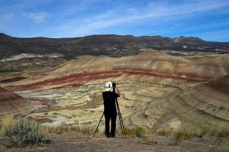San Francisco Bay area resident Brian Martin photographs Painted Hills, a unit of the John Day Fossil Beds National Monument, in preparation for the total lunar eclipse near Mitchell, Oregon, U.S. August 20, 2017. REUTERS/Adrees Latif