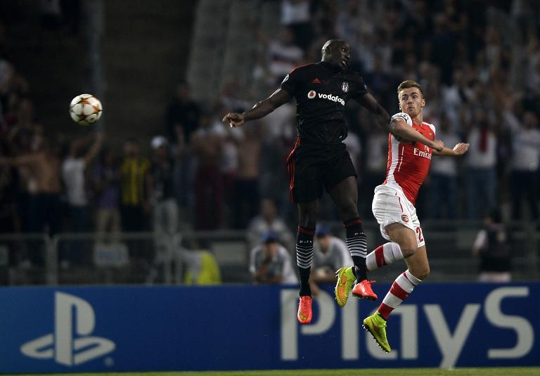 Besiktas's Demba Ba (L) jumps for the ball with Arsenal's Calum Chambers (R) during their UEFA Champions League play-off first leg football match at the Ataturk Olympic Stadium in Istanbul, on August 19, 2014 (AFP Photo/Bulent Kilic)
