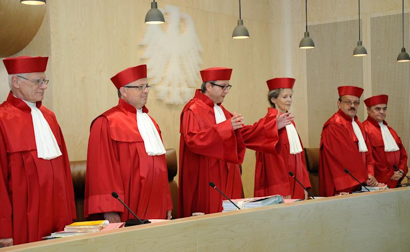 Judges of the second senate of the German Federal Constitutional Court from left: Michael Gerhardt, Peter Huber, President Andreas Vosskuhle, Gertrude Luebbe-Wolff, Herbert Landau and Peter Mueller Ronald stand in a court room in Karlsruhe, Germany, Tuesday July 10, 2012. Germany's highest court is to hear arguments Tuesday against the country signing up to the Europe's emergency bailout fund and a new treaty limiting debt. Opponents of the treaties argue that joining the bailout fund and debt pact for the 17 countries that use the euro would impose limits on the German Parliament's constitutional power to say how taxpayer money is spent. (AP Photo/dapd/ Wittek)