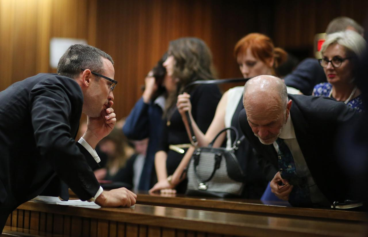 Oscar Pistorius, left, talks with his uncle Arnold Pistorius, right, during his ongoing murder trial in Pretoria, South Africa, Tuesday, May 13, 2014. Pistorius is charged with the shooting death of his girlfriend Reeva Steenkamp on Valentine's Day in 2013. (AP Photo/Themba Hdebe, Pool)
