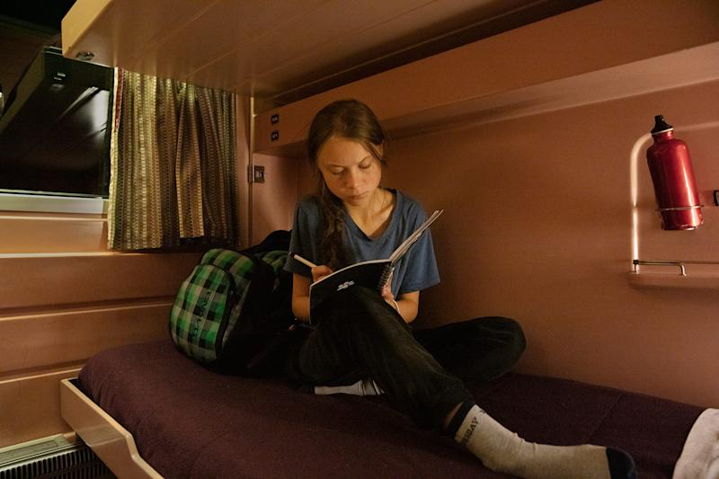 Thunberg writes in her journal on the train as she travels from Lisbon to Madrid for a U.N. climate conference | Evgenia Arbugaeva for TIME