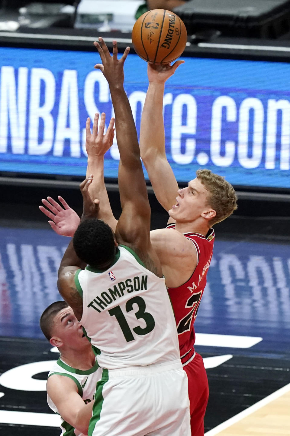 Chicago Bulls forward Lauri Markkanen, right, shoots against Boston Celtics guard Payton Pritchard and center Tristan Thompson (13) during the first half of an NBA basketball game in Chicago, Friday, May 7, 2021. (AP Photo/Nam Y. Huh)