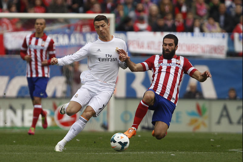 Real's Cristiano Ronaldo, left, in action with Atletico's Arda Turan, right , during a Spanish La Liga soccer match between Atletico de Madrid and Real Madrid at the Vicente Calderon stadium in Madrid, Spain, Sunday, March 2, 2014. (AP Photo/Gabriel Pecot)