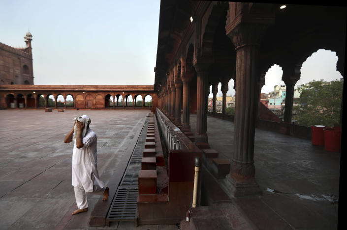 A Muslim wipes his face after performing ablution before prayer on the first day of the holy fasting month of Ramadan at the deserted Jama Masjid, which is usually packed with thousands of devotees, during a nation wide lockdown in place to check the spread of the new coronavirus, in New Delhi, India, April 25, 2020. (AP Photo/Manish Swarup)