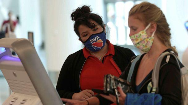 FILE PHOTO: A Southwest Airlines Co. employee wears a protective mask while assisting a passenger at Los Angeles International Airport (LAX) during the outbreak of the coronavirus disease (COVID-19) in Los Angeles, California, U.S., May 23, 2020.  (Patrick Fallon/Reuters)