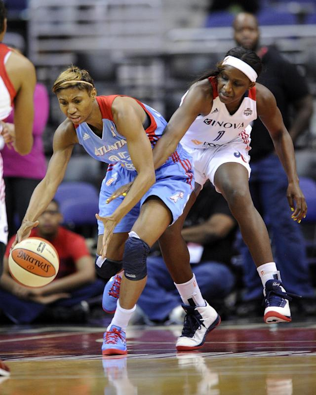 Washington Mystics forward Crystal Langhorne, right, battles for the ball against Atlanta Dream guard Angel McCoughtry, left, during the first half of Game 2 of the WNBA basketball Eastern Conference semifinal series, Saturday, Sept. 21, 2013, in Washington. (AP Photo/Nick Wass)