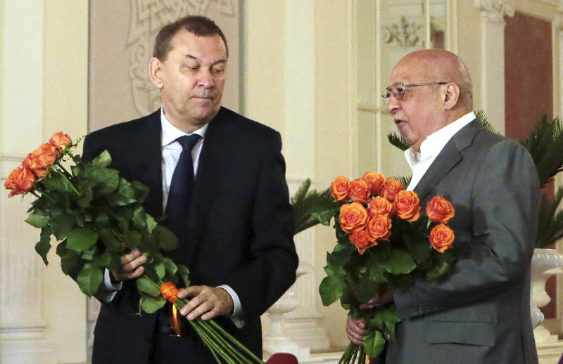 """In this photo made available by The Bolshoi Theater, newly appointed director general of the Bolshoi Theater Vladimir Urin, left, and former director general Anatoly Iksanov talk at a news conference at the theater in Moscow, Tuesday, July 9, 2013. Russian Culture Minister Vladimir Medinsky said Tuesday, July 9, 2013, that Anatoly Iksanov would be replaced by Vladimir Urin, head of another major ballet and opera theater. He said that a """"difficult situation at the theater"""" was the reason for the dismissal. Iksanov, however, was offered to work as Medinsky's adviser in the ministry. (AP Photo/The Bolshoi Theater, Damir Yusupov)"""