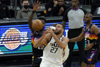 Utah Jazz center Rudy Gobert (27) loses the ball as Phoenix Suns center Deandre Ayton defends during the first half of an NBA basketball game, Wednesday, April 7, 2021, in Phoenix. (AP Photo/Matt York)