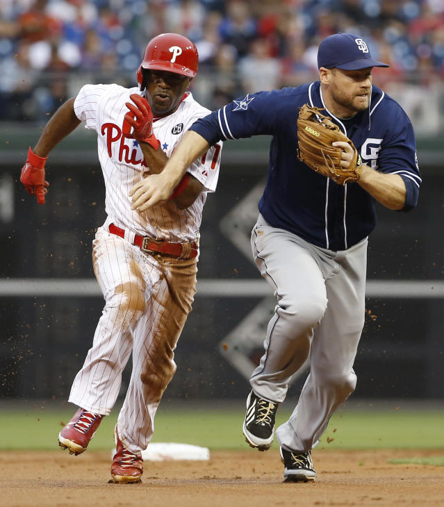 Philadelphia Phillies' Jimmy Rollins, left, brushes past San Diego Padres third baseman Chase Headley to steal to third during the first inning of a baseball game on Wednesday, June 11, 2014, in Philadelphia. Rollins stole second and third base on the same play after the Padres left third uncovered while playing a defensive shift for hitter Ryan Howard. (AP Photo/Matt Slocum)
