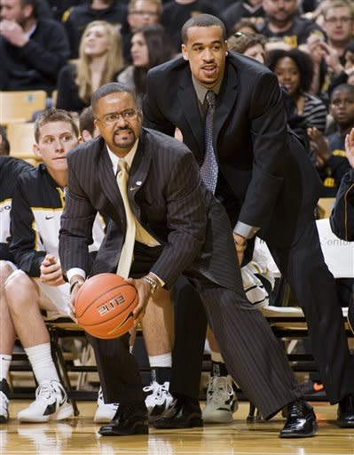 Missouri head coach Frank Haith, left, grabs the ball with help from injured player Lawrence Bowers, right, as it goes out of bounds during the first half of an NCAA college basketball game against Texas Saturday, Jan. 14, 2012, in Columbia, Mo. (AP Photo/L.G. Patterson)