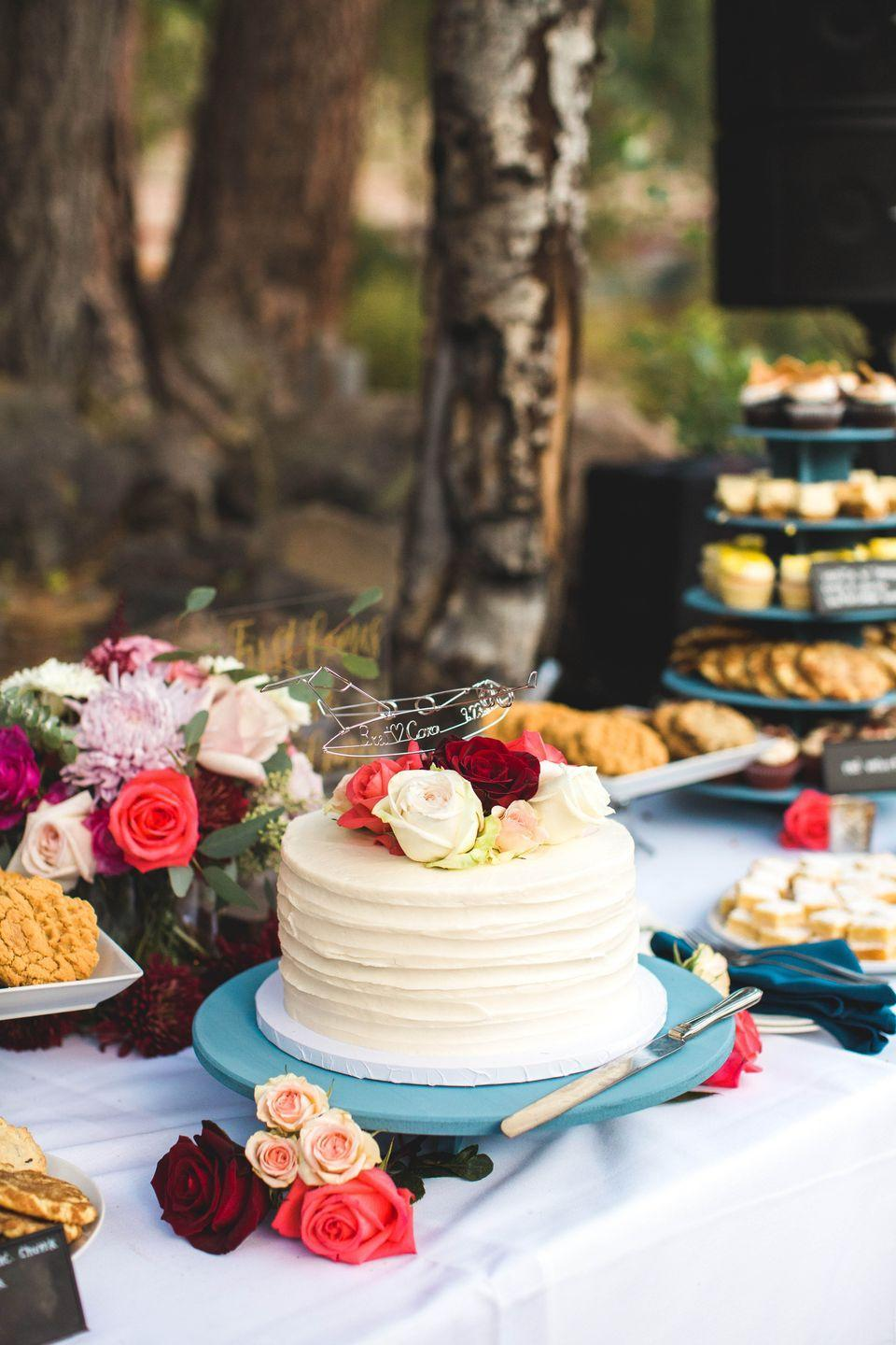 """<p>Adorn the dessert table with in-season flowers (like these from <a href=""""https://www.fiftyflowers.com/"""" rel=""""nofollow noopener"""" target=""""_blank"""" data-ylk=""""slk:Fifty Flowers"""" class=""""link rapid-noclick-resp"""">Fifty Flowers</a>) for a fresh way to display your wedding cake.</p>"""