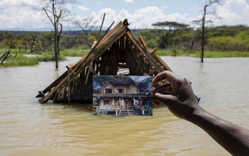 Camp manager James Owuor, holds a photo showing a structure before it was submerged under rising water due to months of unusually heavy rains, in lake Baringo, Kenya.  - BAZ RATNER /Reuters