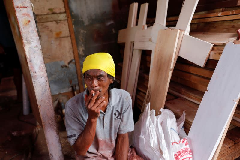 Suherman, a 45-year-old coffin maker, smokes a cigarette while taking a break as he prepares coffins ordered to be donated for the coronavirus disease (COVID-19) victims at a workshop inside a funeral complex in Jakarta