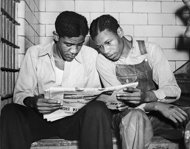 FILE - In this July 16, 1937 file photo, Charlie Weems, left, and Clarence Norris, Scottsboro case defendants, read a newspaper in their Decatur, Ala. jail after Norris was found guilty for a third time by a jury which specified the death penalty. Weems was to be tried a week later. Nine black teenagers known as the Scottsboro Boys were convicted by all-white juries of raping two white women on a train in Alabama in 1931. All but the youngest were sentenced to death, even though one of the women recanted her story. All eventually got out of prison, but only one received a pardon before he died. (AP Photo)
