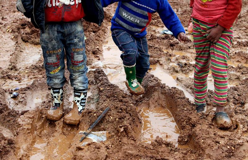 Children who fled the violence in Syria's northern Raqa province, play in the mud at the unofficial refugee camp in al-Saadiyeh (AFP Photo/Anwar Amro)