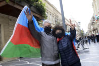 Azerbaijanis with the national flag celebrate after the country's President claimed Azerbaijani forces have taken Shushi, a key city in the Nagorno-Karabakh region that has been under the control of ethnic Armenians for decades in Baku, Azerbaijan, Sunday, Nov. 8, 2020. (AP Photo)